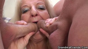A blonde granny swallow off two young guys